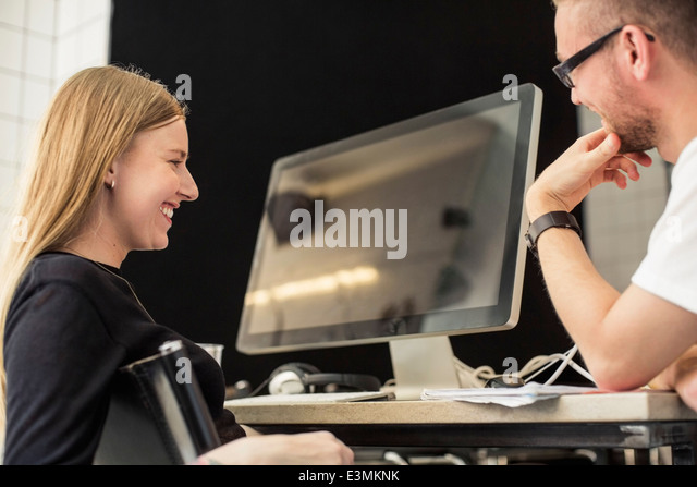 Young businessman and businesswoman looking at computer monitor in creative office - Stock Image
