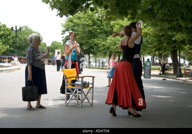 Old Greek woman greets dancers, Spianada, Kerkyra, Corfu, Greece, Europe, - Stock Image