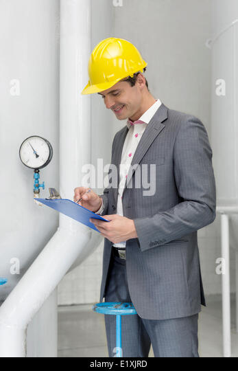 Smiling young male manager writing on clipboard in industry - Stock Image