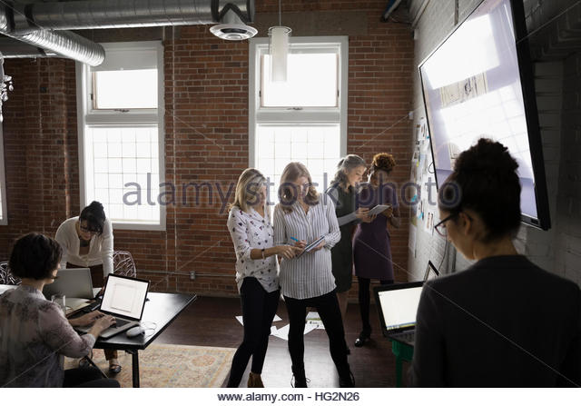 Businesswomen working and brainstorming in conference room - Stock Image