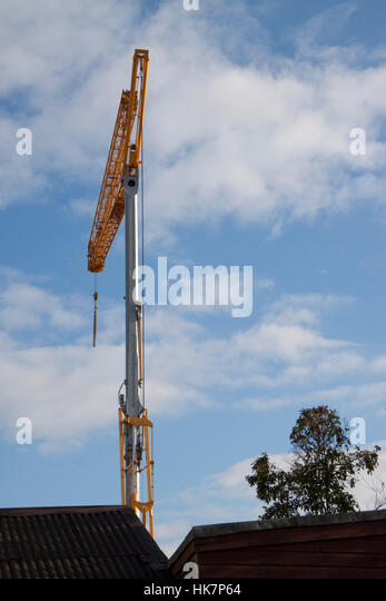 A yellow construction crane against blue sky - Stock Image