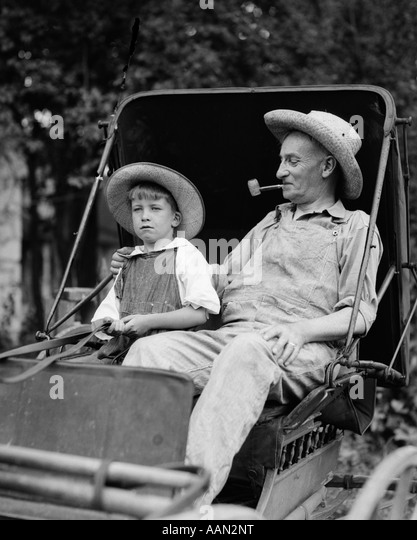 1930s FARM BOY & GRANDFATHER IN OVERALLS & STRAW HATS SITTING IN SMALL BUGGY - Stock Image