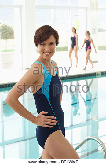 Portrait of smiling women sitting at edge of swimming pool - Stock Image