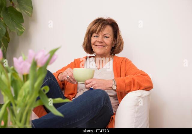 Happy senior woman sitting on sofa and having cup of tea at home, Munich, Bavaria, Germany - Stock-Bilder