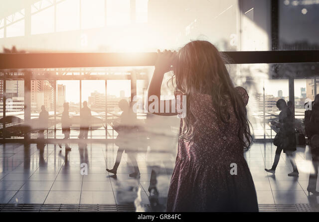 The little girl looking through the window farewell feelings alone. Dark tone color sadness emotions concept. - Stock Image