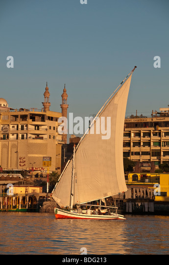 Felucca traditional wooden sailboat on Nile River Aswan Egypt with minarets from Islamic mosque in backgground - Stock Image