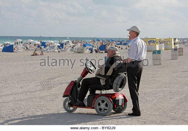 Miami Beach Florida Atlantic Ocean senior man electric wheelchair cart adult son - Stock Image