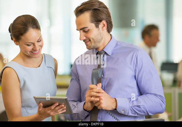 Business people using digital tablet in office - Stock Image