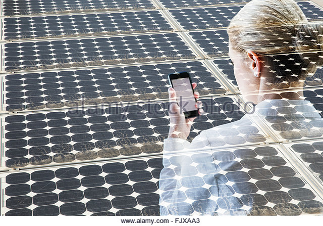 Digital composite businesswoman using cell phone solar panels - Stock Image