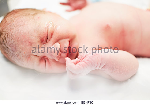 Close up of baby boy crying in crib - Stock Image