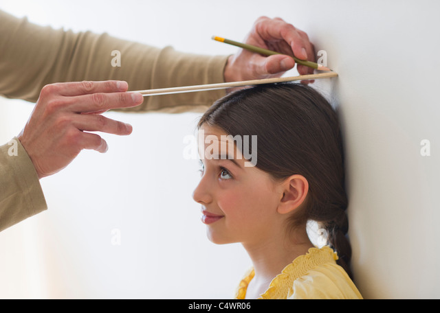 USA, New Jersey, Jersey City, girl (8-9) being measured - Stock Image
