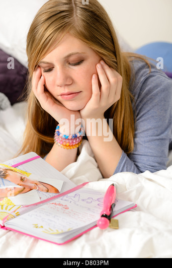 Sad teenage girl lying over her diary because unrequited love - Stock Image