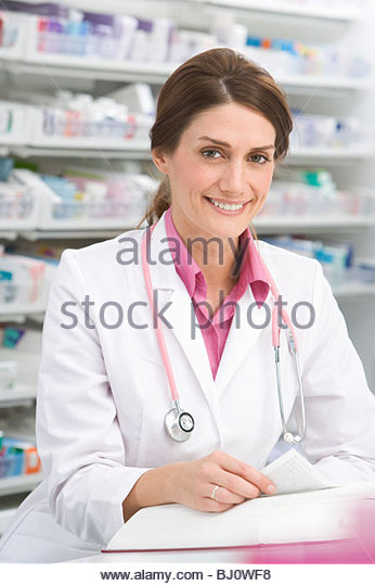 Pharmacist researching medicine in book in pharmacy - Stock Image