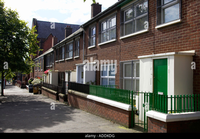 row of red brick terraced houses in inner city urban interface area of belfast with security doors and screened - Stock Image