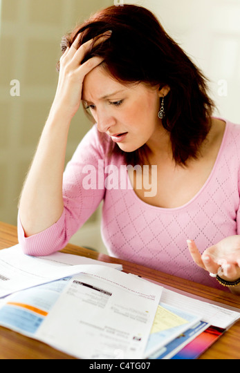 Woman looking at Utility bills - Stock Image