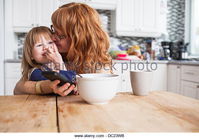 Mother and daughter hugging at breakfast table - Stock-Bilder