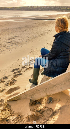young blond female sitting on cabin stairs on beach - Stock Image