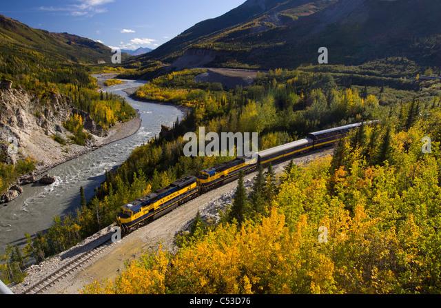 Alaska Railroad passenger train travels along the Nenana River before crossing under the Parks Highway near Mile - Stock Image