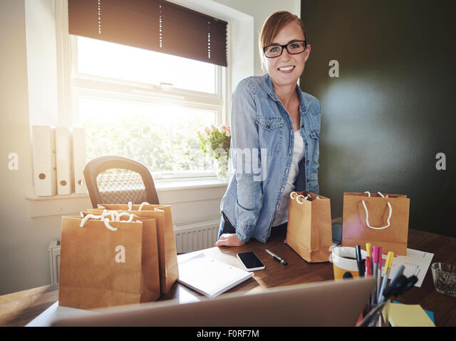 Successful new female entrepreneur standing in her home office leaning on the desk smiling at the camera - Stock-Bilder