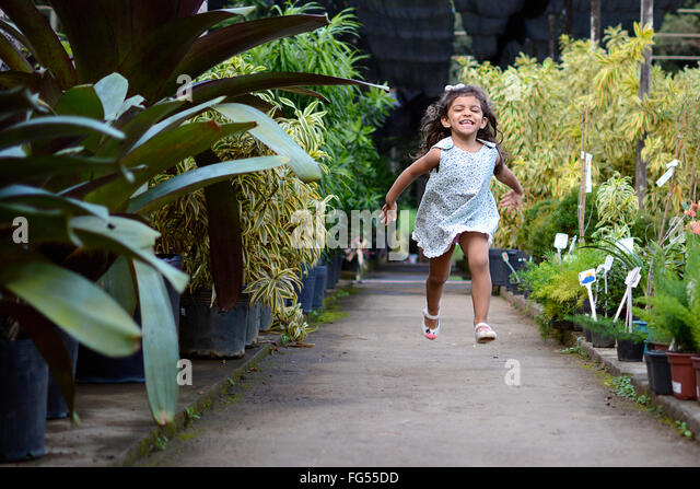 Full Length Of Cheerful Girl Running At Greenhouse - Stock Image