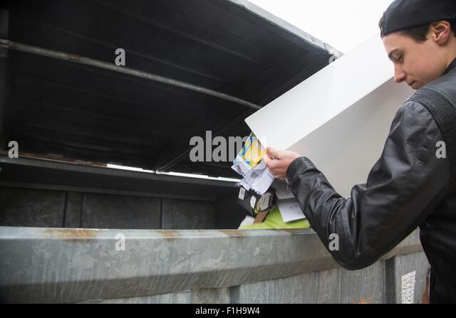 Teenage boy emptying bin with paper waste to recycling bin - Stock Image