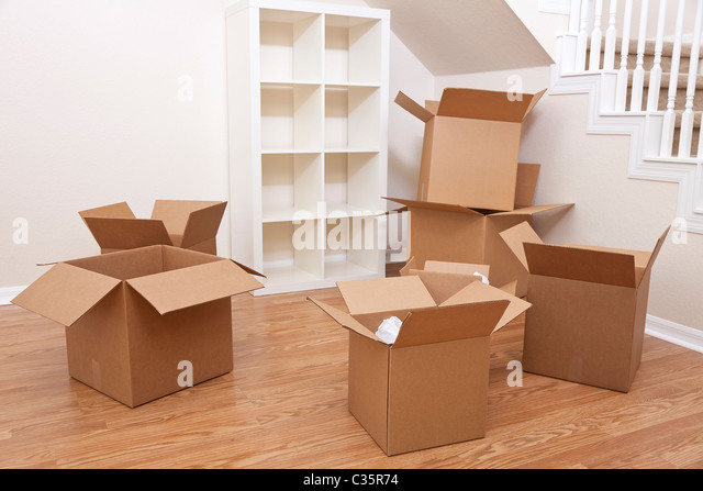 Empty room full of cardboard boxes for moving into a new home. - Stock Image