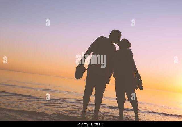 Happy senior couple silhouettes on the beach kissing - Stock-Bilder