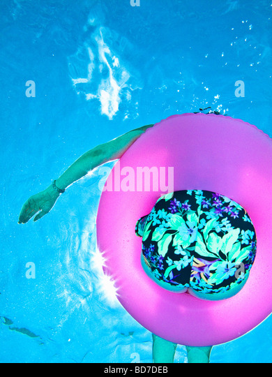 View from below of woman floating in pool - Stock Image