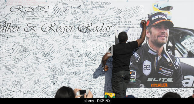 Los Angeles, USA. 8th Dec, 2013. A fan of actor Paul Walker signs on a giant poster at a memorial rally and car - Stock Image