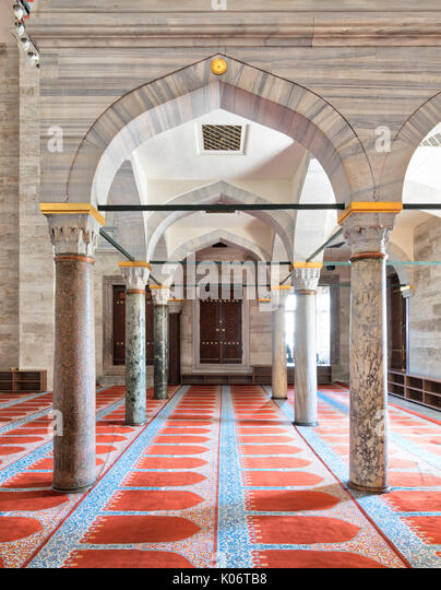 Passage in Sulaymaniye Mosque, with columns, arches and floor covered with red carpet, Istanbul, Turkey - Stock Image