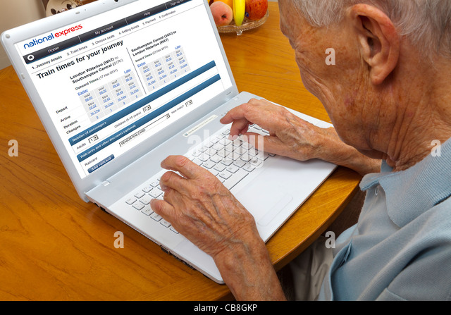 Elderly gentleman surfing the web booking coach travel on a laptop - Stock-Bilder