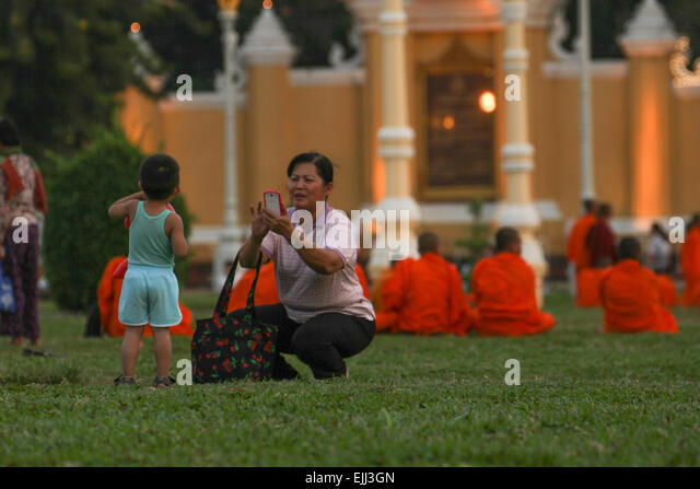 ​A woman takes a photo of a young lad at the  Royal Palace Park in Phom Penh. Credit: David Mbiyu/ Alamy Live News - Stock Image