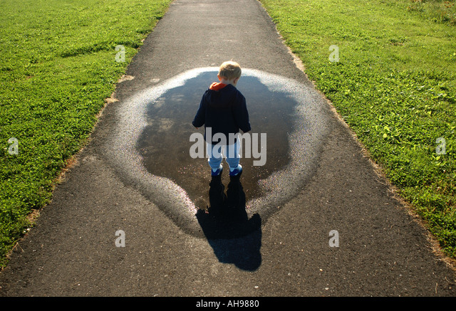small boy looking down at puddle and shadow along a walkway - Stock Image