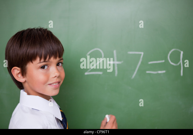 Smiling schoolboy writing an addition - Stock Image