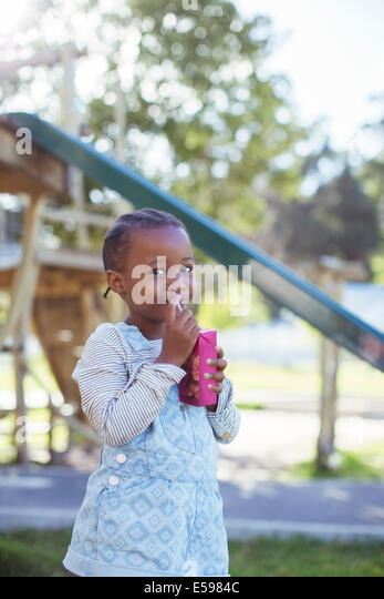 Girl drinking juice box at playground - Stock Image