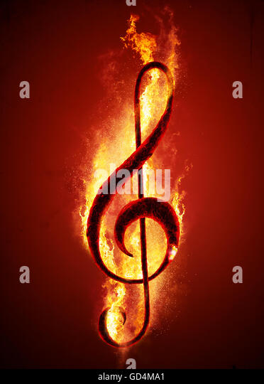 Musical note (treble clef) from hot charcoal on fire. Conceptual image of hot music. - Stock Image