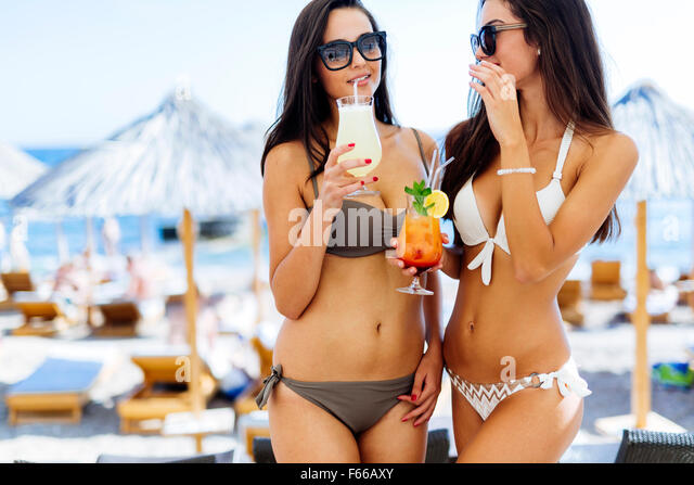 Beautiful women sipping cocktails on beach - Stock Image