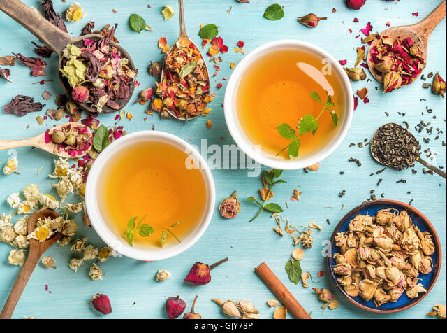Two cups of healthy herbal tea with mint, cinnamon, dried rose and camomile flowers in spoons over blue background, - Stock Image