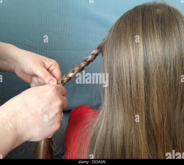 Mother making a braid - Stock-Bilder