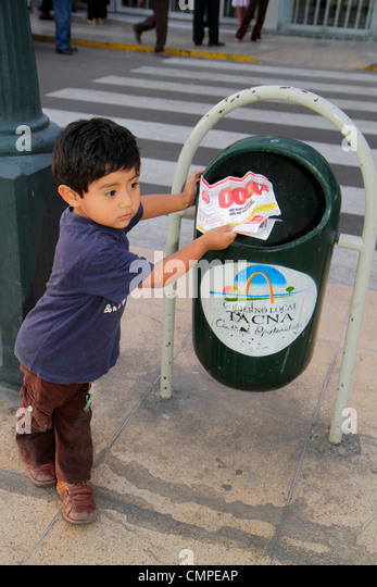 Peru Tacna Avenida San Martin Plaza de Armas Hispanic boy child preschooler trash can city sanitation paper flyer - Stock Image