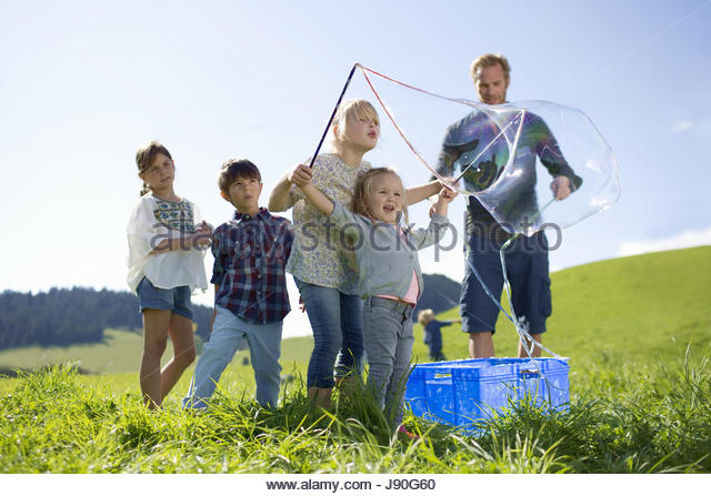 Father And Children Making Giant Bubbles In Countryside - Stock-Bilder