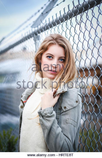 Young blonde woman by a fence - Stock Image