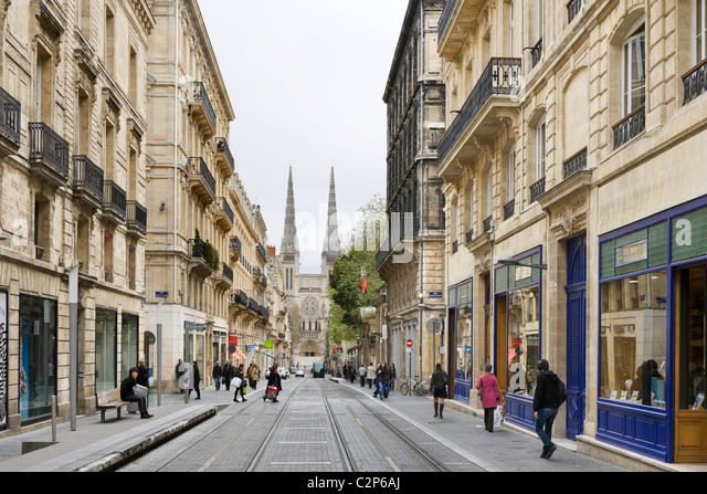 Shops on Rue Vital-Carles with spires of the Cathedral St Andre in background, Quartier St Pierre, Bordeaux, Aquitaine, - Stock Image