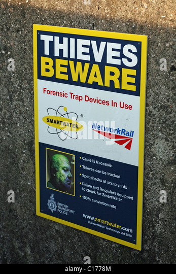 A sign saying thieves beware that Smartwater forensic trap devices are in use on a newrork rail railway line - Stock Image
