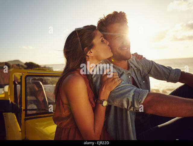 Romantic young couple sitting on the hood of their car while out on a roadtrip. Beautiful young woman kissing her - Stock Image