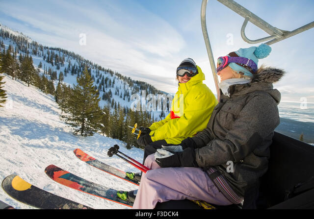 Couple in skiwear sitting on ski lift - Stock Image