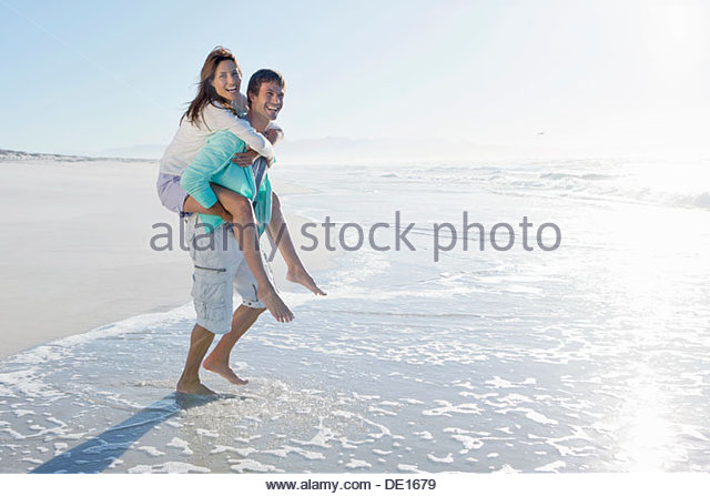 Man piggybacking wife in surf on sunny beach - Stock Image