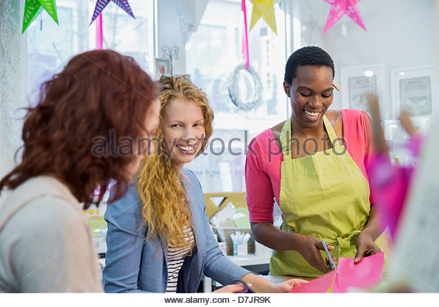 Female small business owner teaching customers in store - Stock-Bilder