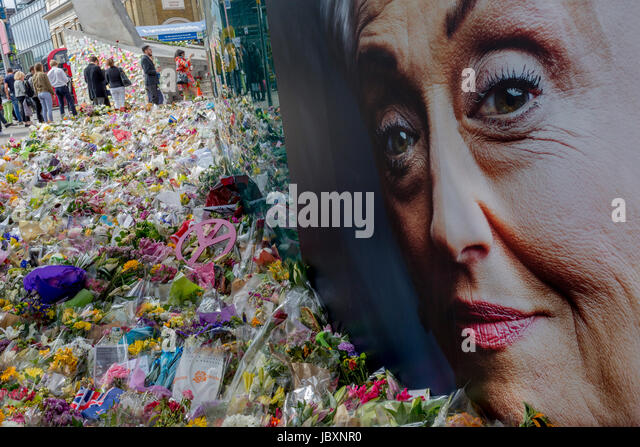 The advertising face of a middle-aged lady symbolises compassion and sympathy at the shrine of flowers and compassionate - Stock Image
