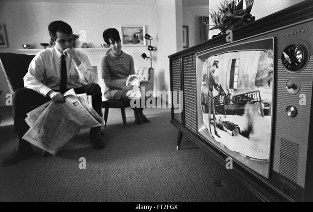 Vietnam War. Couple watching film footage of the Vietnam War on a television in their living room, February 1968 - Stock Image